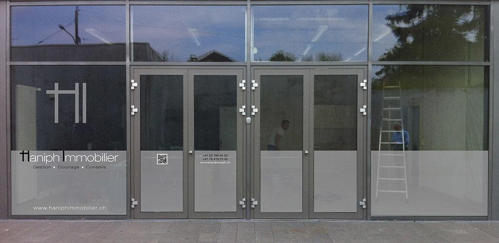 Marquage publicitaire pour agence immobilière. Pose de films dépolis en sous-verre, identification par textes et logo en sur-verre.