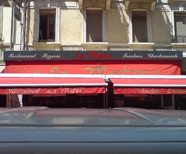 Réalisation et pose de logo et lettrage sur enseigne de restaurant.