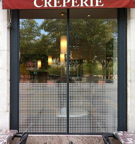 Film opaque et translucide pour fenêtres, laissant filtrer la lumière. Déco en petits carrés pour confidentialité d'un restaurant.
