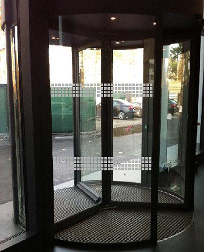 Décoration d'une entrée d'immeuble à porte tournante. Découpe de petits carrés en film verre sablé, pour un résultat sécuritaire.