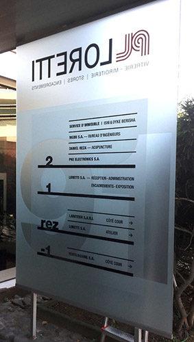 Signalétique sur totem en verre pour porte d'accès d'un immeuble. Films verre sablé recto-verso. Marquage des textes.