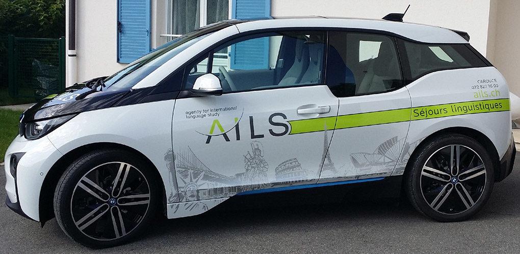 Marquage publicitaire sur véhicule BMW électrique. Décoration en autocollant découpé.