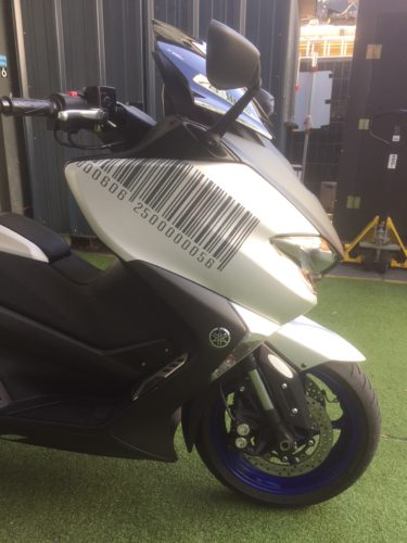 Petit travail de déco sympa sur scooter, création d'un code barre sur mesure avec un positionnement adapté à la carrosserie. Autocollant découpé anthracite.