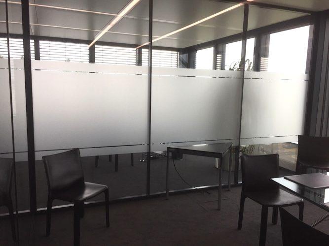 Application dans une salle de conférence, de films de confidentialité. Adhésif verre dépoli.