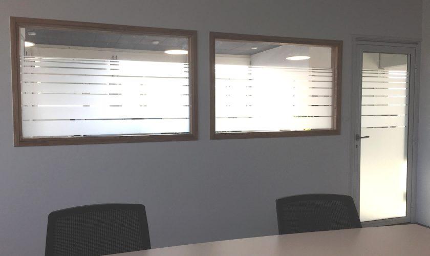Application dans une salle de conférence, de films de confidentialité. Filets découpés en lignes dégradées dans de l'adhésif verre dépoli.