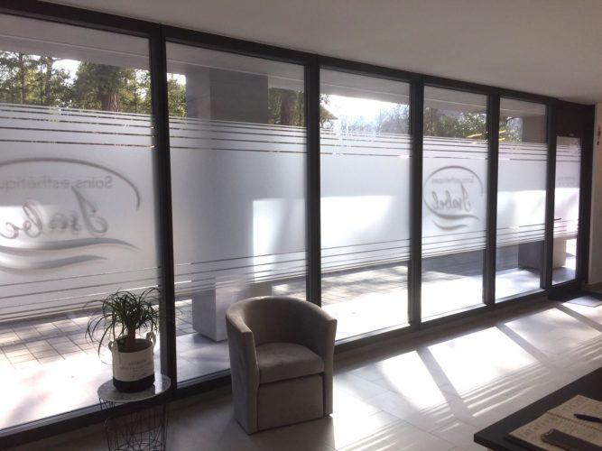 Adhésif de confidentialité verre sablé posé à l'intérieur. Pose des logo et textes à l'extérieur.